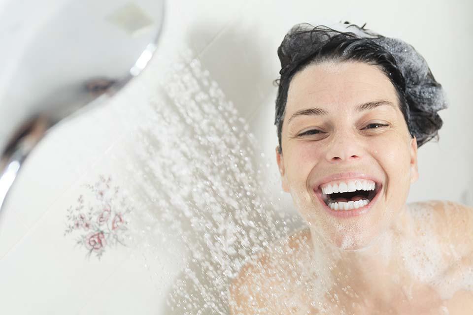 Shower woman. Happy smiling woman washing shoulder showering in